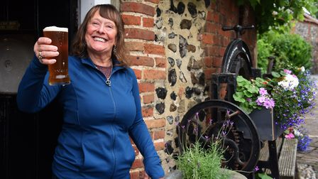 Happy landlady Rita McCluskey serving drinks from the doorway of the re-opened Adam & Eve, with some