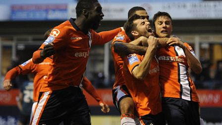Luton goalscorer Alex Lawless is mobbed after despatching Wolves to earn an FA Cup trip to Norwich C