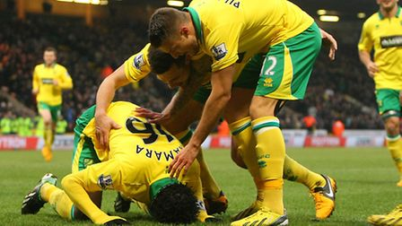 Goalscorer Kei Kamara kisses the Carrow Road turf before being mobbed by his team-mates, following h