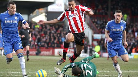 Tom Adeyemi is brought down by Chelsea goalkeeper Ross Turnbull to earn Brentford a fourth round pen