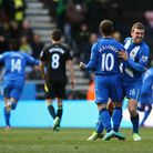 Shaun Maloney and James McArthur celebrate Wigan's winner as goalscorer Arouna Kone runs away in cel