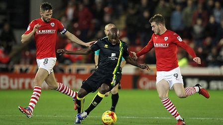 Barnsley striker Sam Winnall (right) fights for the ball with Norwich City's Youssouf Mulumbu and Ty