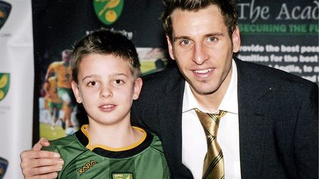A young Angus Gunn pictured with former Norwich City star - and now academy coach - Darren Huckerby.