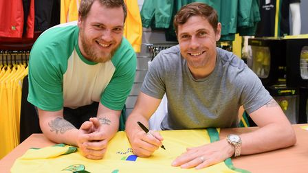 Former Norwich City player, Grant Holt, signs a shirt for fan Ben Royall from Lowestoft, at the NCFC