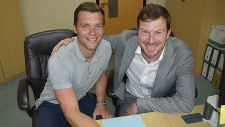 Jonny Howson signs on the dotted line for Middlesbrough, watched by their chief executive, Neil Baus