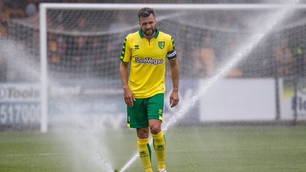 Russell Martin of Norwich City gets soaked as the sprinklers come on during the Pre-season Friendly