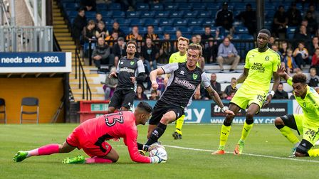 James Maddison of Norwich City challenges Goalkeeper Dimitar Mitov of Cambridge United during the Pr