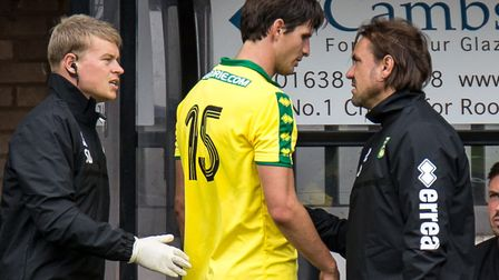 Timm Klose started as part of a back three but limped off at Cambridge, pictured speaking to head co