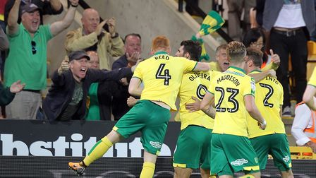 The Canaries players mob Oliveira after he opened the scoring at Carrow Road. Picture: Paul Chestert