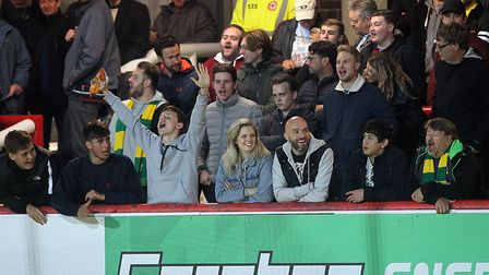 The traveling Norwich fans before the Carabao Cup match at Griffin Park, London. Picture by Paul Che