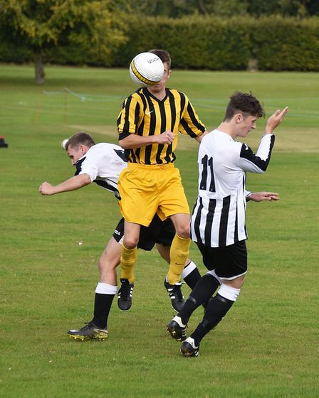 A Beccles player (yellow) wins the ball during the game at Acle. Picture: ANTONY KELLY