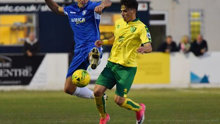 Savvas Mourgos of Norwich City U23s is challenged by Lowestoft striker Jake Reed. Picture: James Bas