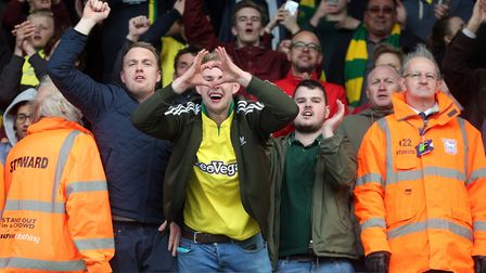 The traveling Norwich fans celebrate victory at the end of the Sky Bet Championship match at Portman