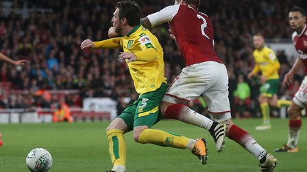 James Husband of Norwich is brought down in the area by Mathieu Debuchy of Arsenal but no penalty is