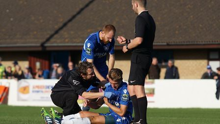 Lowestoft Town player Sam Borrer receiving treatment from physio Colin Whiteman after a blow to the