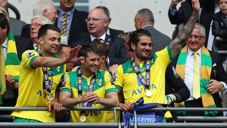 Happy scenes at the end with, from left, Russell Martin, Wes Hoolahan and Bradley Johnson. Picture: