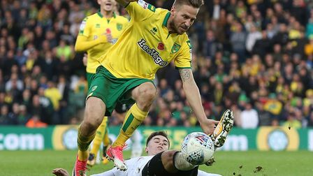 Norwich City full-back Marco Stiepermann and Derby County's Tom Lawrence battle for the ball at Carr