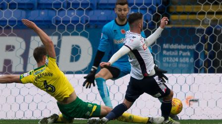 Gary Madine nips in ahead of Christoph Zimmermann to put Bolton in front. Picture: Russell Hart/Focu