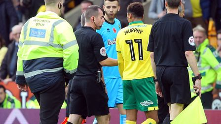 Josh Murphy and Angus Gunn continue the protest with referee Peter Bankes after a penalty was not aw