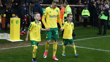 James Maddison leads out the mascots, including Ethan Thomas, before Norwich City's Championship cla