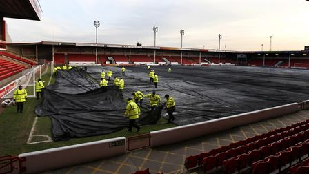 Groundstaff at Walsall re-cover the pitch before their clash against Norwich City was called off in