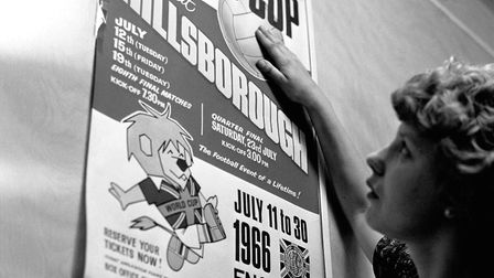 A Sheffield Wednesday employee sticks up a poster advertising the 1966 World Cup games to be played