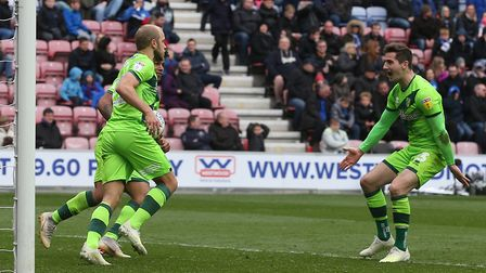 Kenny McLean, right, celebrates after setting up Teemu Pukki, left, for City's equaliser at Wigan