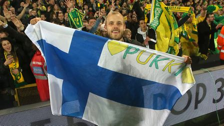 Teemu Pukki celebrates promotion with the Norwich City fans at Carrow Road, and the Finnish flag. Pi