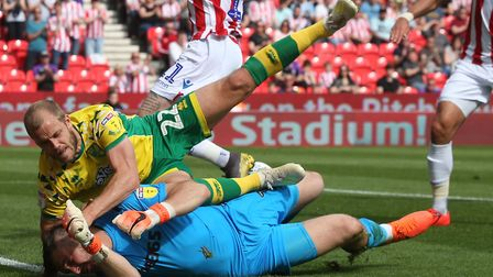 Norwich City striker Teemu Pukki ends up in a tangle with Jack Butland, after the Stoke keeper saved