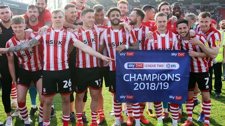 Jason Shackell, sixth from left, with Harry Toffolo on his shoulders, as Lincoln celebrate winning t