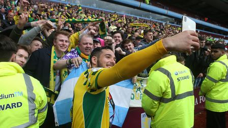Emiliano Buendia of Norwich celebrates winning the championship with the traveling Norwich fans at t
