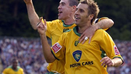 Andrew Hughes celebrates with Darren Huckerby, as the Norwich City forward scores at Brighton. Photo