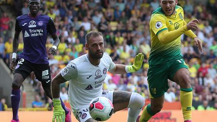Emiliano Buendia of Norwich tries to take the ball round Baptiste Reynet of Toulouse but shows his f