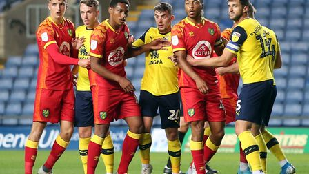 Akin Famewo leads the way for Norwich City (in red) at a corner during the EFL Trophy opener at Oxfo