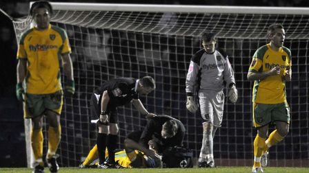 Norwich's Gary Doherty receives attention after suffering a head injury in the build-up to the Bury