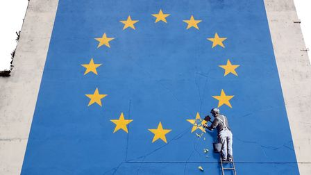 A view of a mural by artist Banksy of a workman removing a star from the EU flag which appeared yest