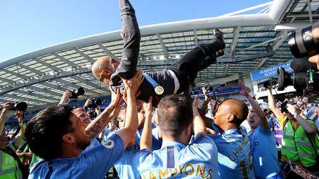 Manchester City manager Pep Guardiola is lifted up by his players whilst celebrating winning the tit