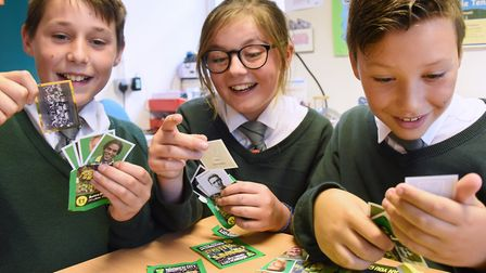 Year Six children at Firside Junior School enjoying opening the NCFC stickers to collect by the East