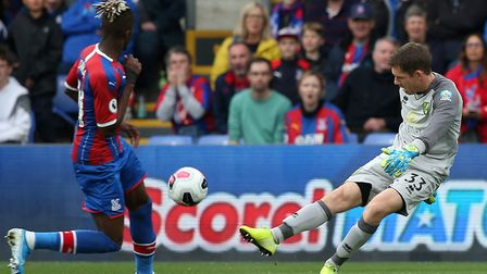 Norwich City goalkeeper Michael McGovern clears the ball under pressure from Crystal Palace ace Wilf