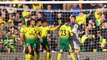 Max Aarons (number two) and the Norwich City players congratulate Michael McGovern on his penalty sa