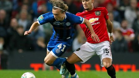 Rochdale's Luke Matheson, left, and Manchester United's Andreas Pereira battle for the ball at Old T