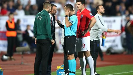 Match referee Ivan Bebek speaks to England manager Gareth Southgate with regards to racist chanting
