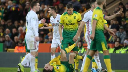 Kenny McLean lies injured after Chris Basham's poor challenge which initially resulted in a red card