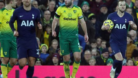 Norwich City captain Grant Hanley gathers his thoughts as Harry Kane celebrates his equaliser for To