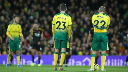 The Norwich players look dejected as the Wolves players celebrate their sides 2nd goal during the Pr