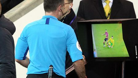 Referee Paul Tierney checks VAR at the side of the pitch for a possible red card offence by Ben Godf