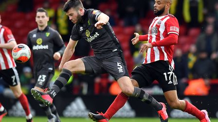Norwich City's Grant Hanley (left) and Sheffield United's David McGoldrick battle for the ball. Pict