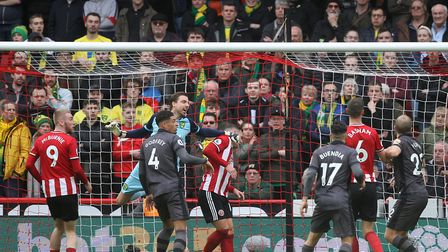 Canaries keeper Tim Krul makes contact with Sheffield United goal-scorer Billy Sharp as he punches c