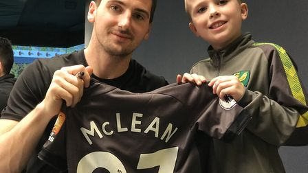 Eight year old Rylan Honeyman from Norwich gets his shirt signed by city midfielder Kenny McLean at