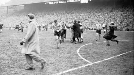 Terry Bly runs head down from the pitch as Luton fans rush to the St Andrews turf to celebrate Luton